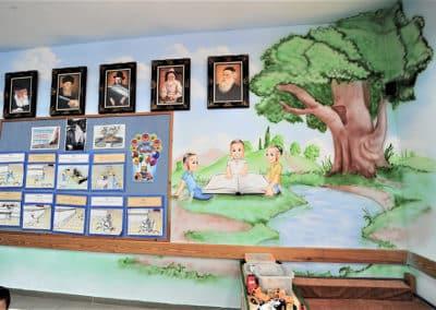 ציור קיר של ילדים יושבים עם ספר
