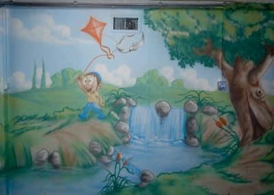 ציורי קיר לחדרי ילדים - ילד עם עפיפון רץ ליד מפל קטן
